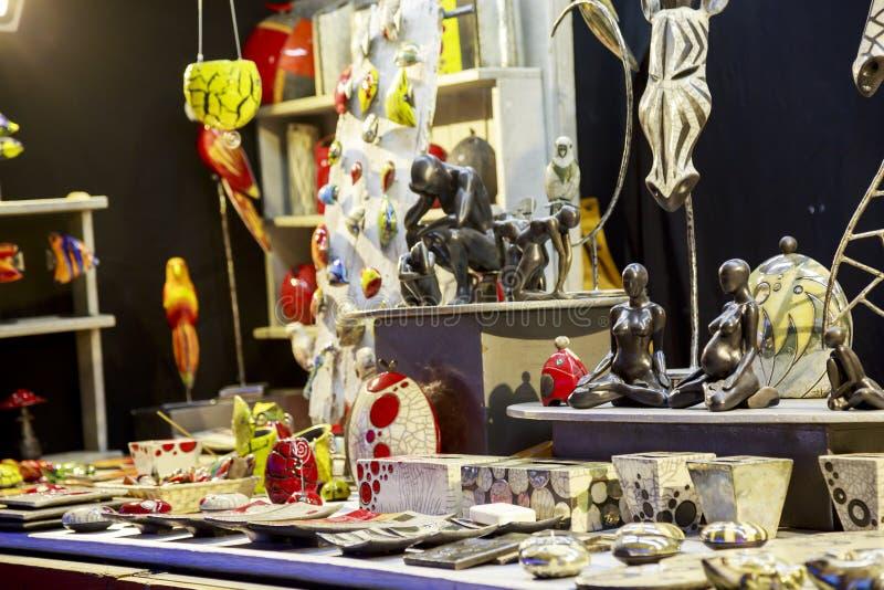 Schöne keramische Skulptur und anderes Zubehör eines Handwerkers, der ein hölzernes Häuschen auf Wechselstrom hält lizenzfreie stockfotos