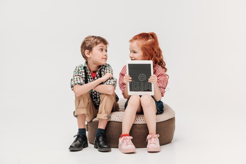 schöne Kinder, die einander betrachten und digitale Tablette mit leerem Bildschirm zeigen lizenzfreies stockfoto