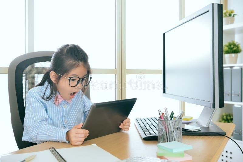 Schöne Kinderbüroangestellter, der Auflage betrachtet lizenzfreie stockbilder