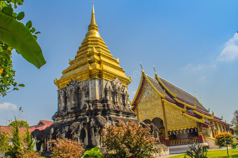Schöne Kirche und goldenes Lanna-Ähnliches chedi herein gestützt durch Reihen von Elefant-förmigen Strebepfeilern bei Wat Chiang  lizenzfreies stockfoto