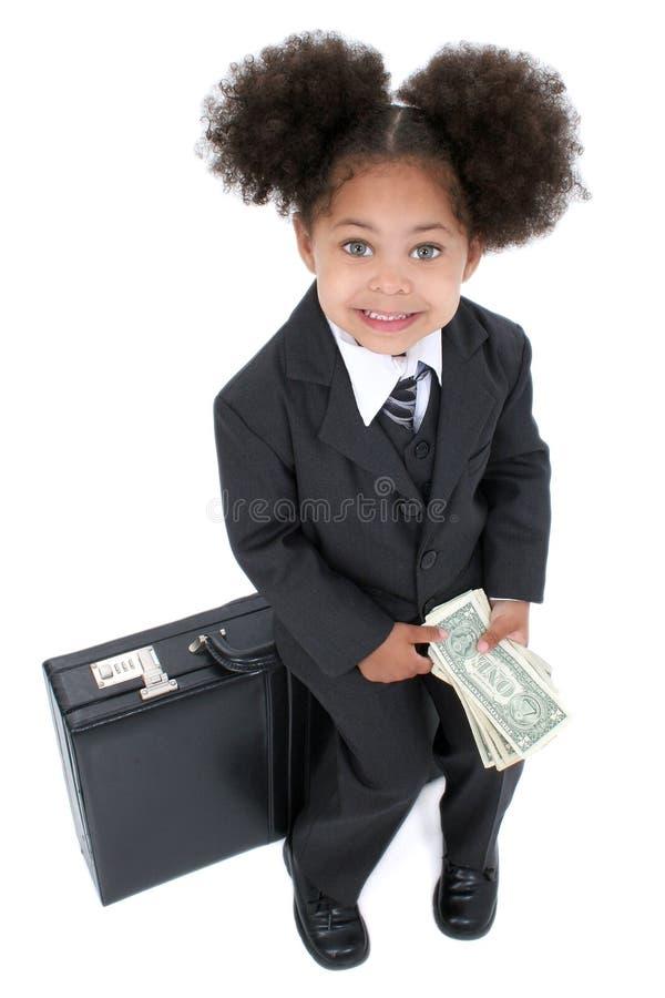 Schöne kleine Geschäftsfrau, die auf Aktenkoffer mit Geld sitzt stockfotografie