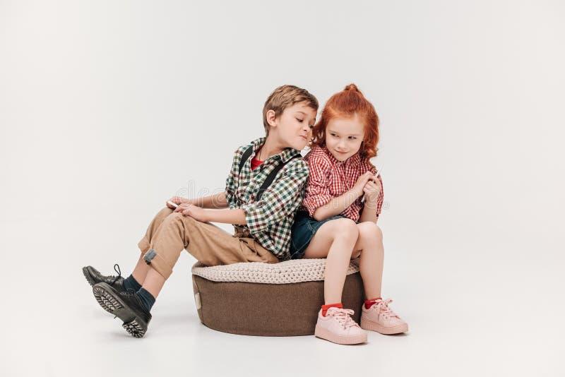 schöne kleine Kinder, die digitale Tablette und Smartphone verwenden stockfotos