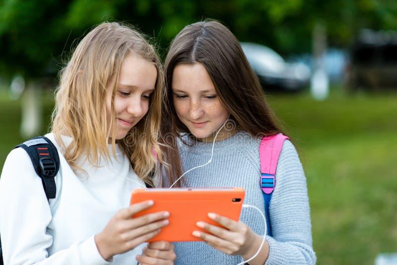 Schöne kleine zwei Mädchen Sommer in der Natur In ihren Händen hält eine Tablette Aufpassende hörende Musik des Videos Schaut soz lizenzfreie stockbilder