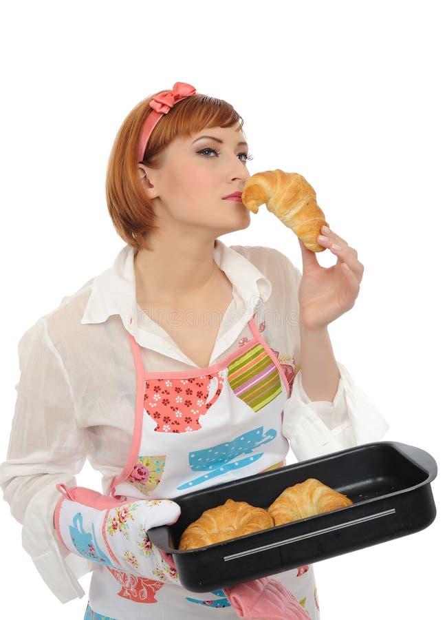 Schöne kochende Frau mit Hörnchenbrot lizenzfreies stockfoto
