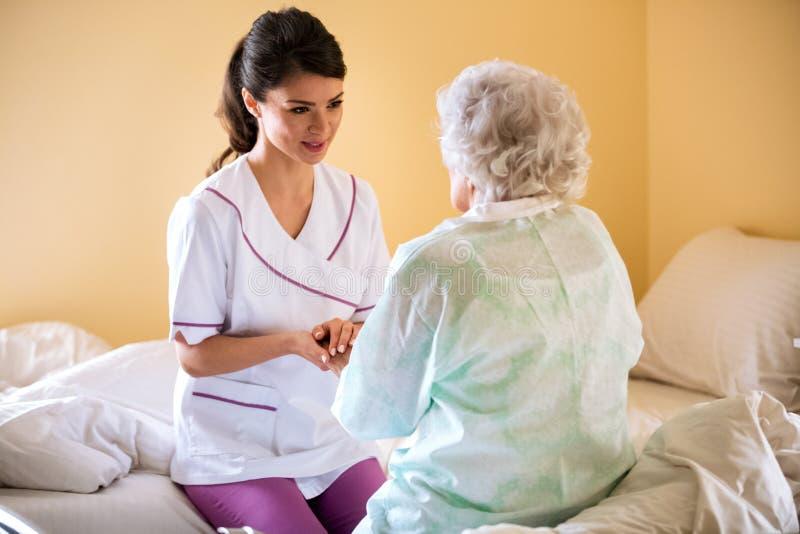 Schöne Krankenschwester, die Hand alten älteren Patienten und des Komforts h hält stockfoto