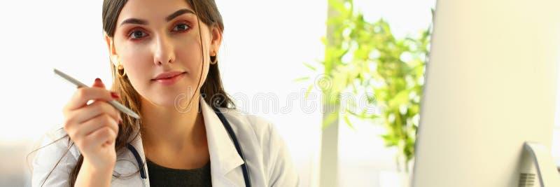 Schöne lächelnde Ärztin am Arbeitsplatzporträt stockbild