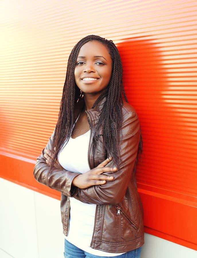 Schöne lächelnde afrikanische Frau des Porträts, die eine Lederjacke trägt lizenzfreies stockbild