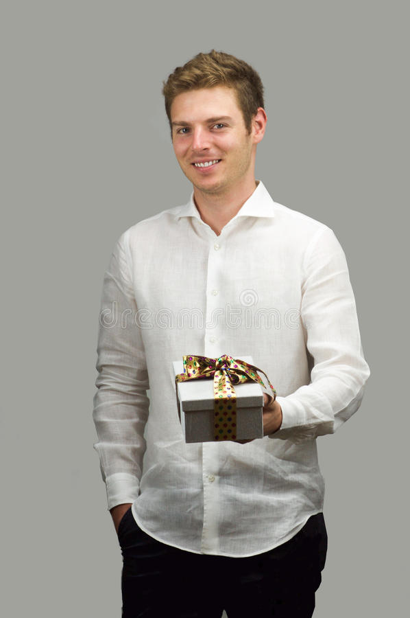 Schöne lächelnde anbietende nette Geschenkbox des jungen Mannes stockfotografie