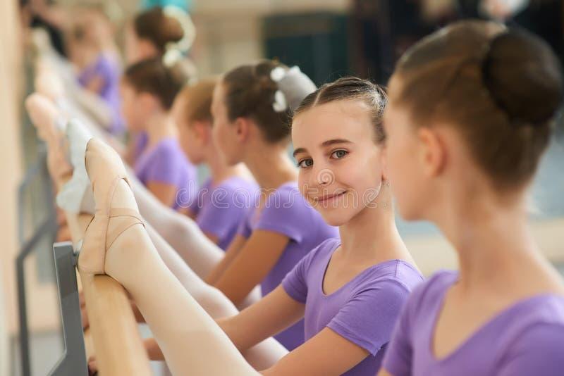 Schöne lächelnde Ballerina, die Bein ausdehnt stockbild