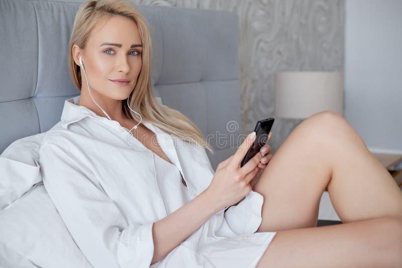 Schöne, lächelnde blonde Frau, die im weißen Bett liegt und einen Smartphone verwendet lizenzfreie stockfotos