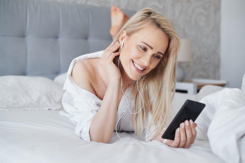 Schöne, lächelnde blonde Frau, die im weißen Bett liegt und einen Smartphone verwendet stockfoto