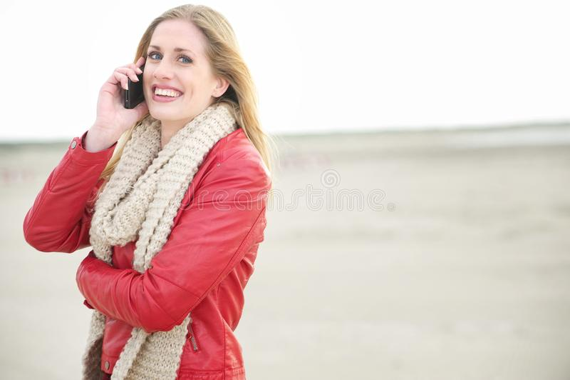 Schöne lächelnde blonde Frau, die am Telefon spricht lizenzfreies stockfoto