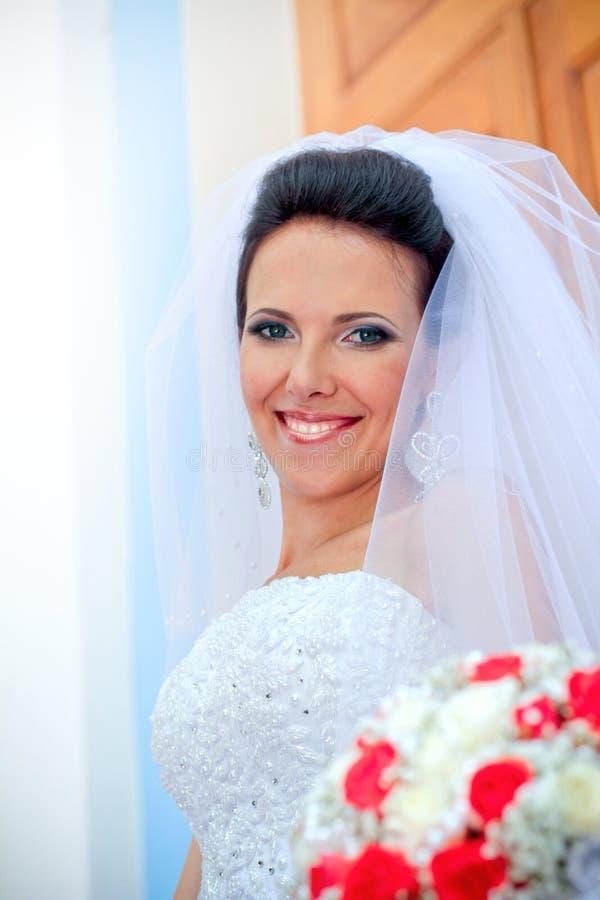 Schöne lächelnde Braut mit Blumenstrauß stockfotografie