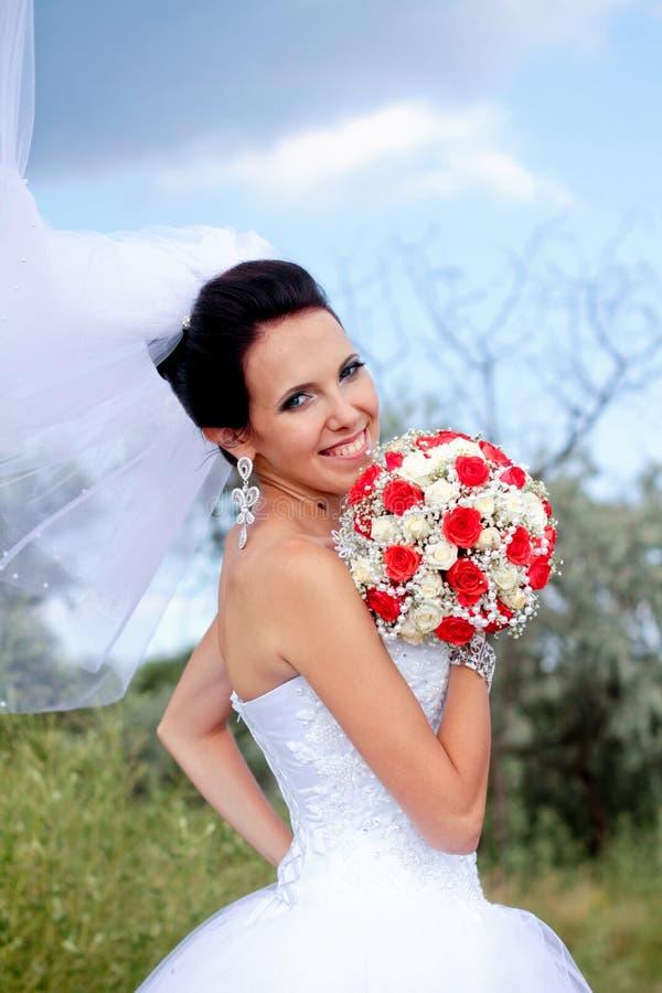 Schöne lächelnde Braut mit Blumenstrauß lizenzfreie stockbilder
