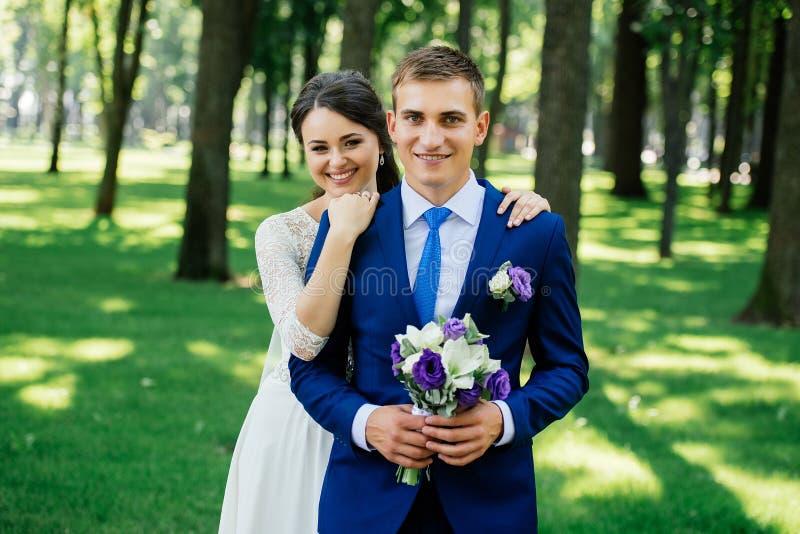 Schöne lächelnde Braut- und Bräutigamumarmungen Yong im Park Braut umfaßt den Bräutigam Paare in der Liebe am Hochzeitstag stockfoto