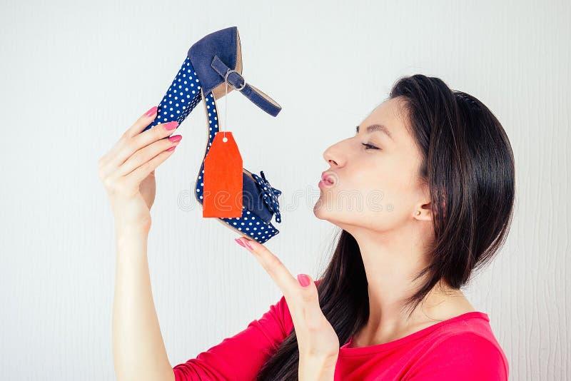 Schöne lächelnde Brunette Frau Shopaholic küsst eine stilvolle Schuhe mit einem roten Etikett , Tab , Tal in ihrer Hand lizenzfreie stockbilder