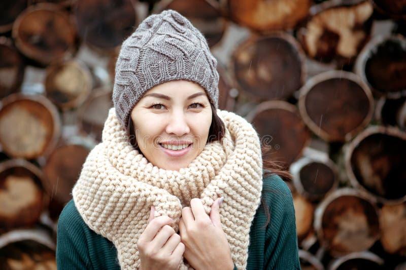 Schöne lächelnde Brunettefrau, die gestrickten Schal und Hut trägt stockfotografie