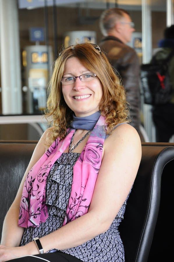 Schöne lächelnde Dame, die am Flughafen wartet lizenzfreies stockfoto