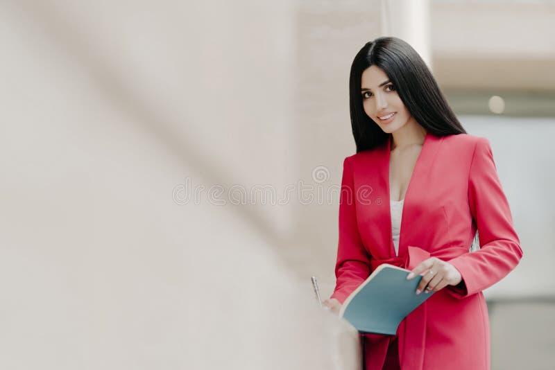 Schöne lächelnde Dame im eleganten roten Kostüm, schreibt einige Anmerkungen in Notizblock, steht extern, Kopienraum auf linker S stockbilder