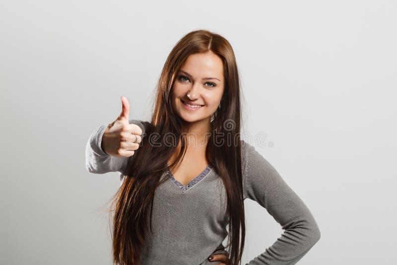 Schöne lächelnde Frau auf grauem Hintergrund Daumen oben lizenzfreies stockfoto