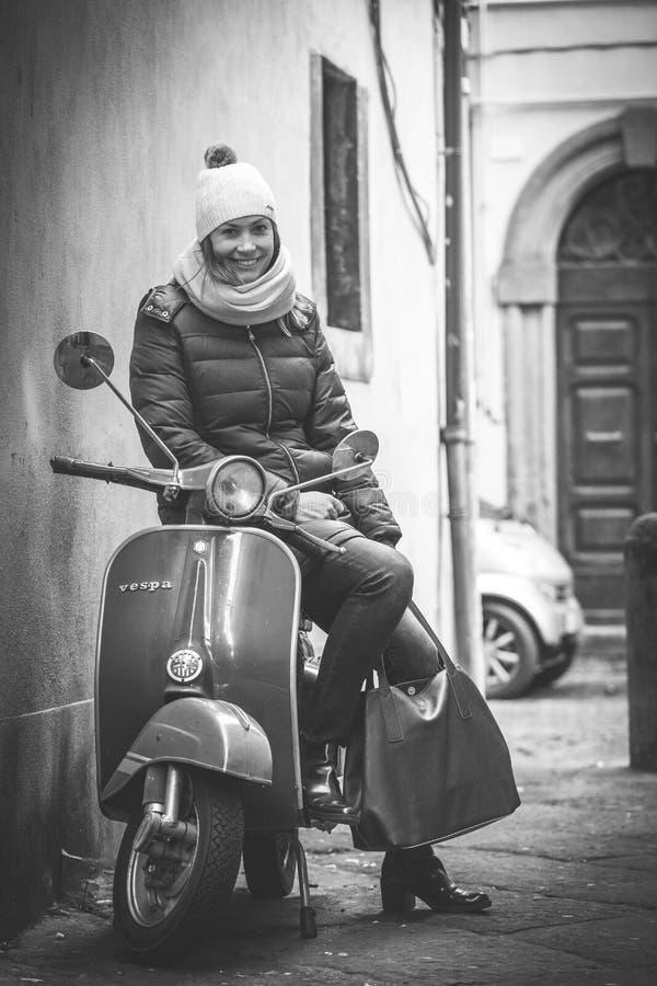 Schöne lächelnde Frau, die auf einem alten italienischen Motorrad sitzt lizenzfreie stockfotografie