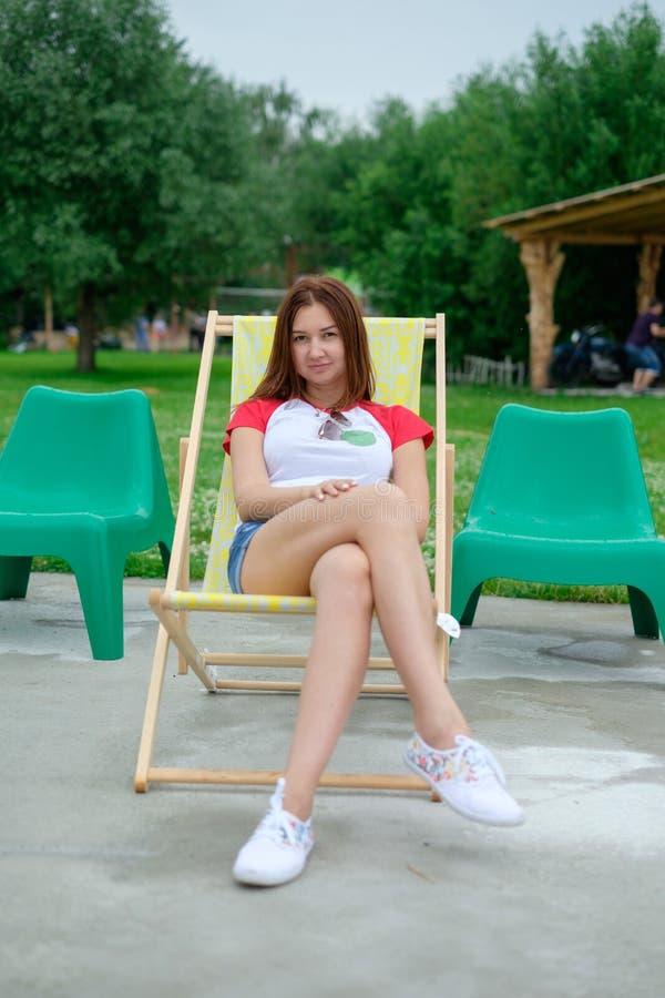 Schöne lächelnde Frau, die auf einem Ruhesessel im Freien liegt Sie ist absolut glücklich lizenzfreie stockfotos