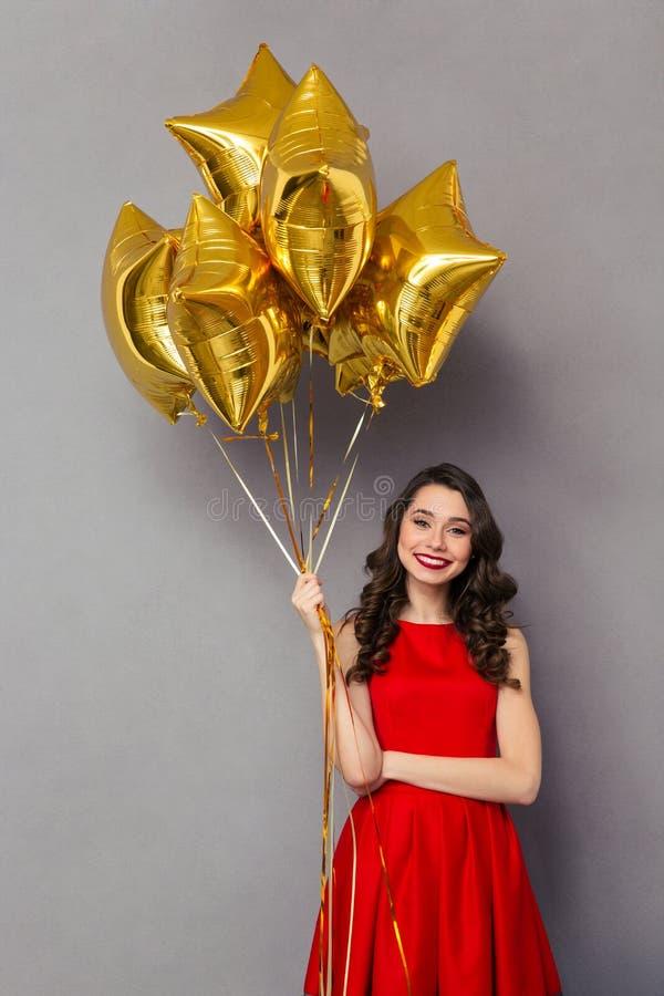 Schöne lächelnde Frau, die Ballone hält lizenzfreies stockbild