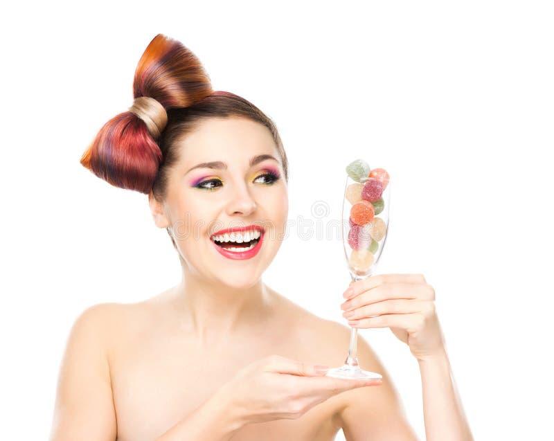 Schöne lächelnde Frau, die ein Weinglas mit Süßigkeiten hält lizenzfreies stockfoto