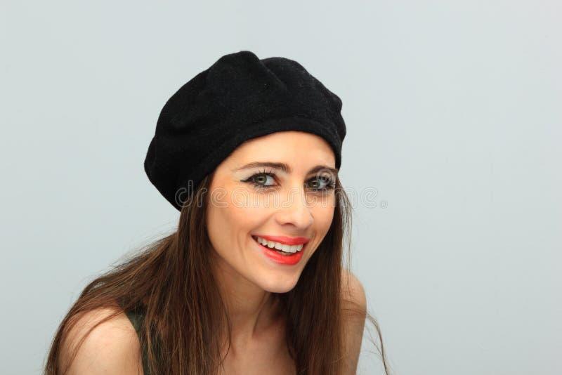 Schöne lächelnde Frau, die einen Baretthut trägt lizenzfreies stockfoto