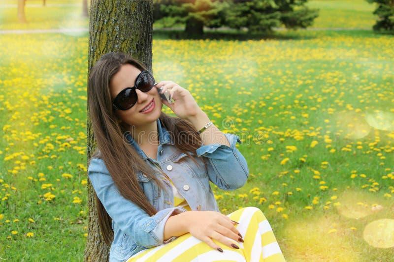 Schöne lächelnde Frau, die am Handy spricht lizenzfreie stockbilder