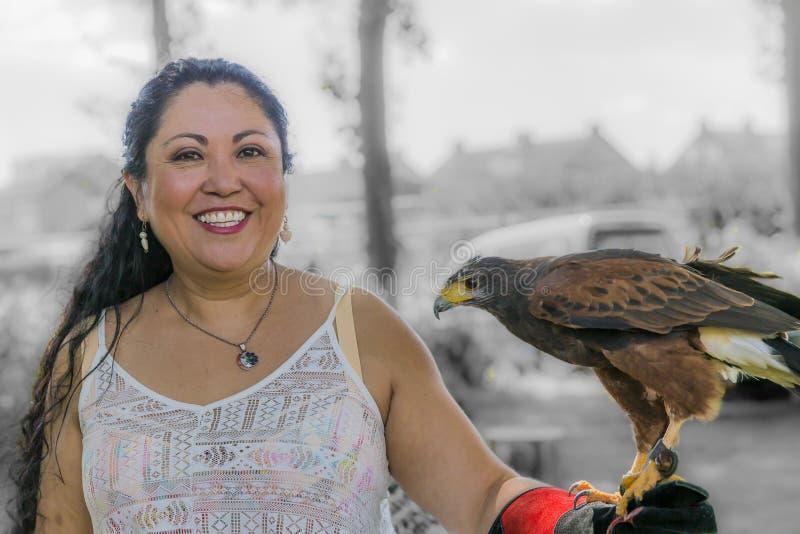 Schöne lächelnde Frau, die mit einem Adlerfalken in ihrer Hand aufwirft lizenzfreies stockbild