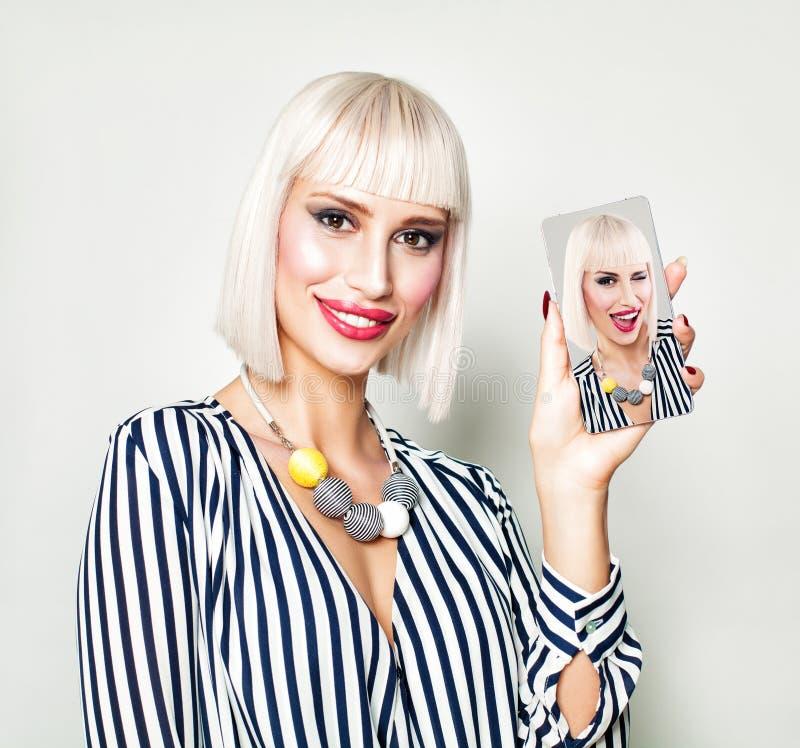 Schöne lächelnde Frau, die selfie Foto am intelligenten Telefon zeigt stockfoto