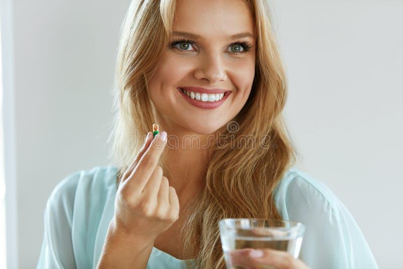 Schöne lächelnde Frau, die Vitamin-Pille einnimmt Diätetische Ergänzung stockfoto
