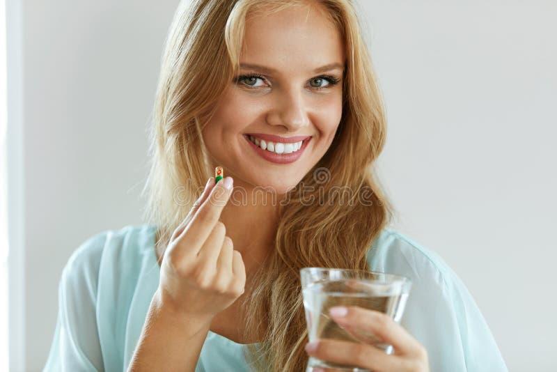 Schöne lächelnde Frau, die Vitamin-Pille einnimmt Diätetische Ergänzung stockfotos
