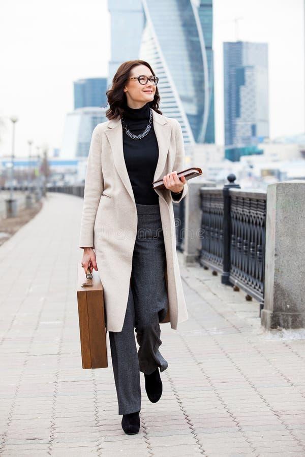 Schöne lächelnde Frau in einem weißen Mantel mit einem Holzetui und einem b lizenzfreies stockfoto