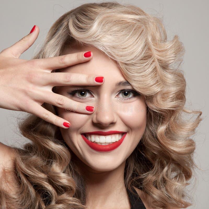 Schöne lächelnde Frau. Gesundes langes gelocktes Haar lizenzfreies stockbild