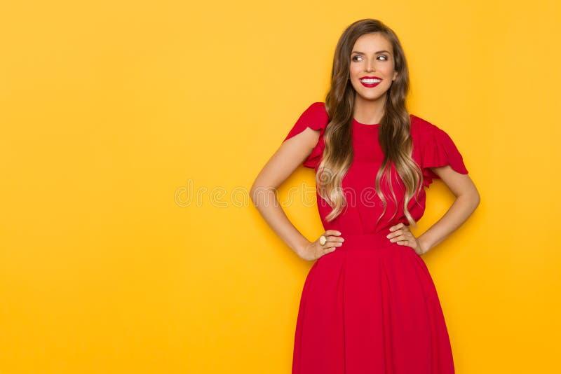 Schöne lächelnde Frau im roten Kleid ist Händchenhalten auf Hüfte und weg schauen stockbild