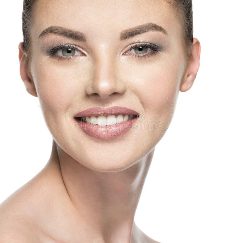 Schöne lächelnde Frau interessiert sich für das Hautgesicht -, das auf wh lokalisiert wird lizenzfreie stockfotografie