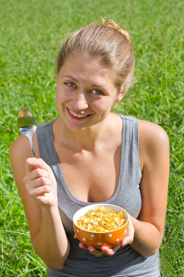 Schöne lächelnde Frau mit Corn-Flakes stockbilder