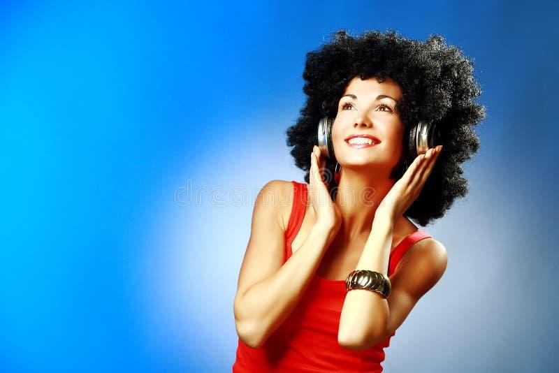 Schöne lächelnde Frau mit dem Afrohaar hören Musik mit Kopfhörern stockfotos