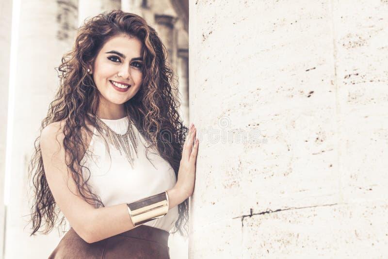 Schöne lächelnde Frau mit dem gelockten Haar Art und Weiseblick lizenzfreie stockfotos