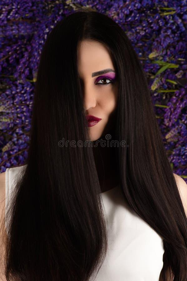 Schöne lächelnde Frau mit dem geraden Haar auf Hintergrund von Lupine blüht lizenzfreie stockbilder