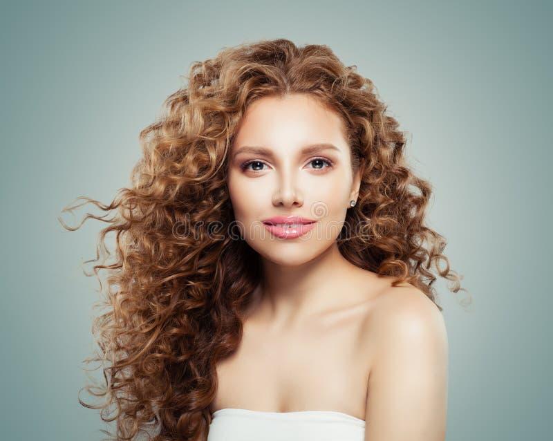 Schöne lächelnde Frau mit dem gesunden gelockten Haar auf grauem Hintergrund Rothaarigemädchen lizenzfreies stockbild