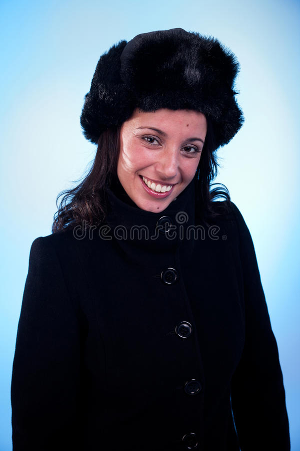 Schöne lächelnde Frau, mit einer Schutzkappe und einem Mantel lizenzfreie stockfotografie