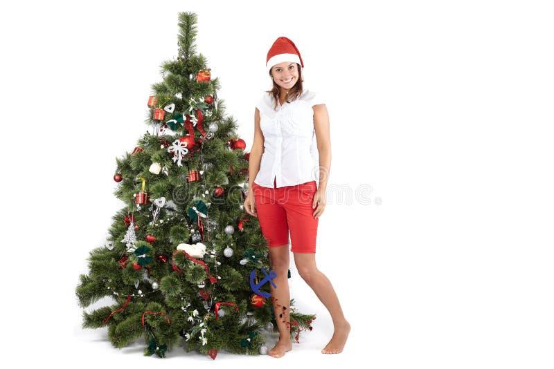 Schöne lächelnde Frau in Sankt-Kappe nahe bei dem Weihnachtsbaum, auf weißem stockbild
