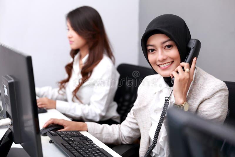 Schöne lächelnde Geschäftsfrau beim Beantworten des Telefons stockbilder