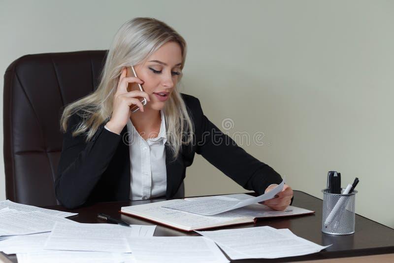 Schöne lächelnde Geschäftsfrau, die an ihrem Schreibtisch mit Dokumenten arbeitet und am Telefon spricht stockfoto