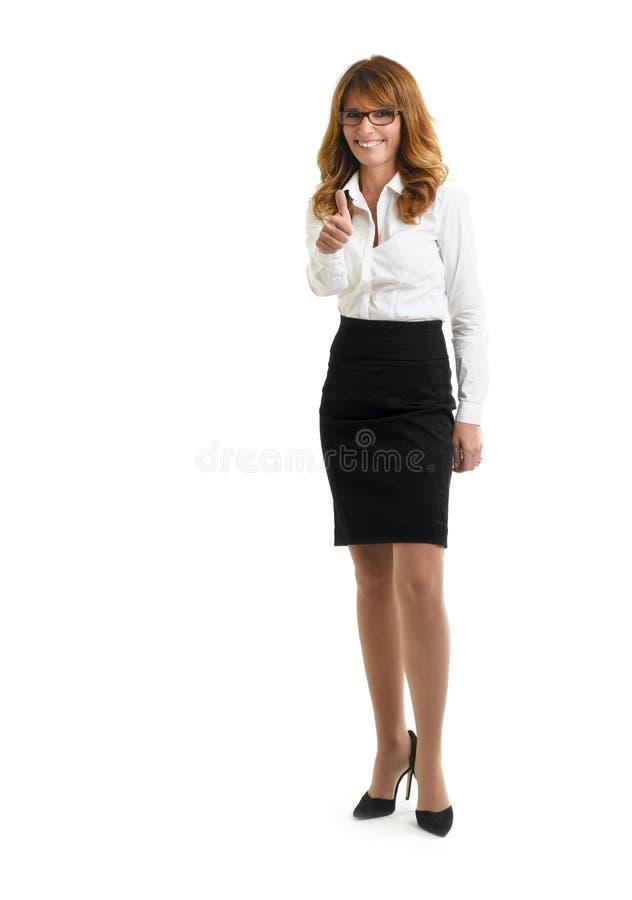 Schöne lächelnde Geschäftsfrau, die sich Daumen zeigt lizenzfreie stockfotografie