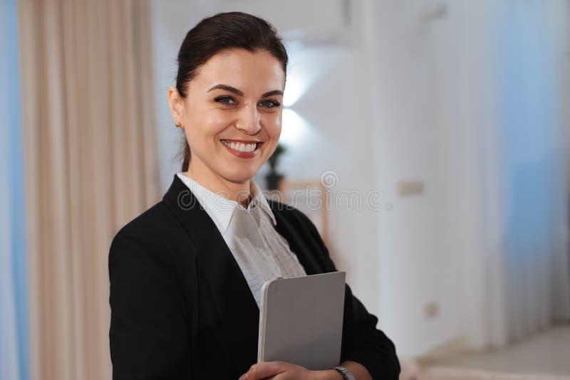Schöne lächelnde große Frau mit einer schönen Zahnimmobilienagentur, die herein eine elektronische Tablette und ein Lächeln groß  lizenzfreie stockfotografie