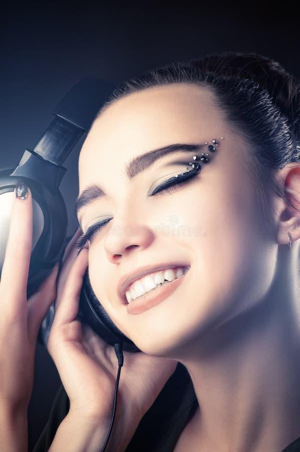 Schöne lächelnde hörende Musik des Mädchens durch Kopfhörer stockfotos